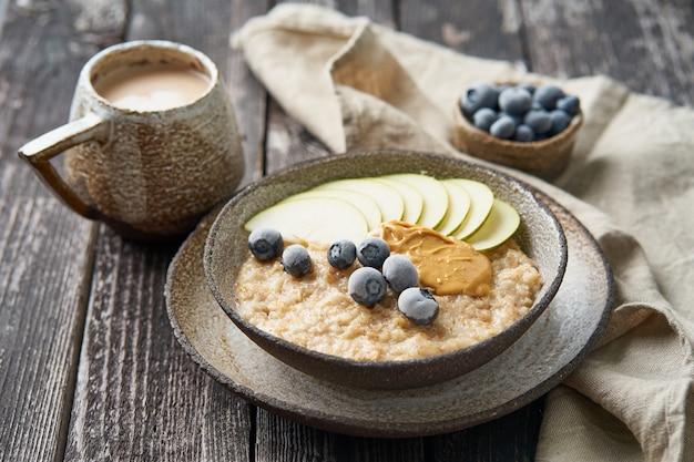 Farina d'avena, porridge sano in una grande ciotola con frutta, bacche per colazione, tazza di cacao. vista laterale