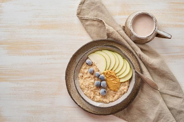 Farina d'avena, porridge sano in una grande ciotola con frutta e bacche per colazione, tazza di cacao.