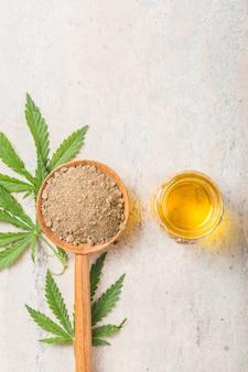Farina di canapa in cucchiaio di legno e olio essenziale di canapa. copia spazio. cannabis cbd.