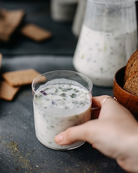 Farina di colombe verdi con yogurt alle erbe bollito su grigio