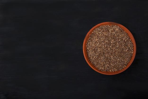 Farina di farro in una tazza di argilla su un fondo di legno nero