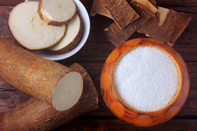 Farina di tapioca in ciotola di legno sulla tavola di legno rustica, accanto al taglio e la manioca affettata