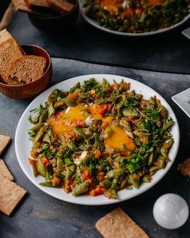Farina di verdure affettata farina di verdure colorate fritte con pane pagnotte uova all'interno del piatto bianco su grigio