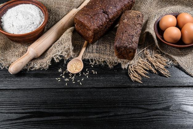 Farina in una ciotola di legno sul tavolo di legno scuro con spighette di grano, uova