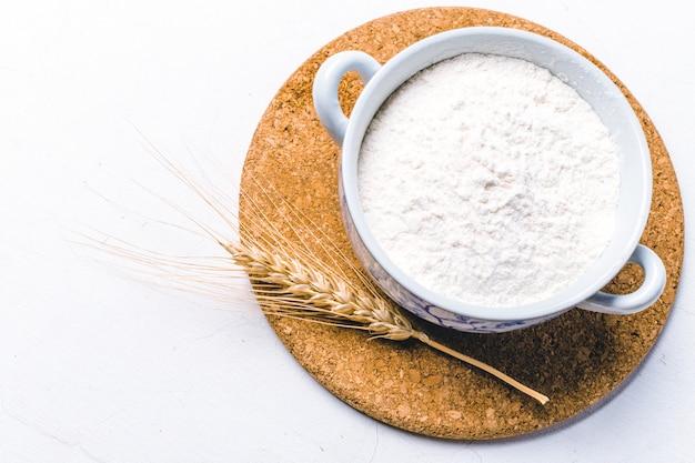 Farina integrale in una ciotola con spighe di grano su bianco
