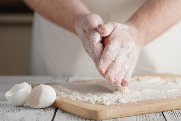 Farina sul tavolo di legno chiaro come sfondo con la mano dell'uomo