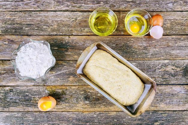 Farina sullo sfondo di cottura con uovo crudo, mattarello e spiga di grano