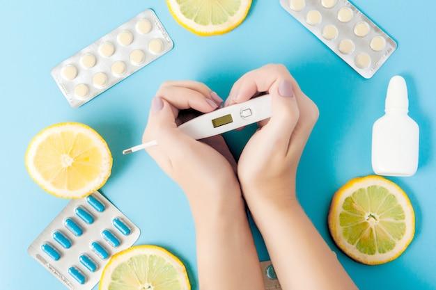 Farmaci, pillole, termometro, medicina tradizionale per il trattamento di raffreddori, influenza, calore su una parete blu. mantenimento dell'immunità. malattie stagionali vista dall'alto. medicina distesi