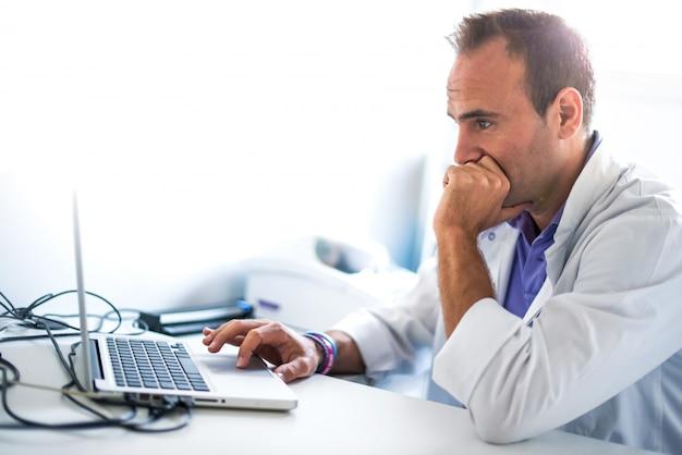 Farmacista adulto dell'uomo in farmacia che lavora con il suo computer portatile