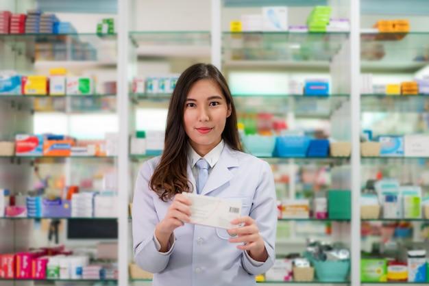 Farmacista asiatico della giovane donna con un medicinebox adorabile adorabile della tenuta di sorriso e esaminare macchina fotografica nella farmacia della farmacia.