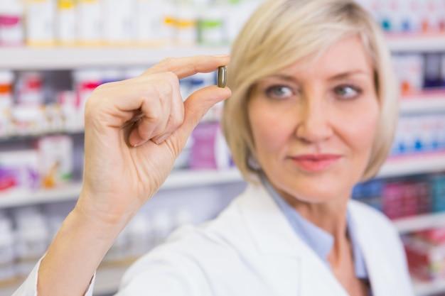 Farmacista biondo in camici che mostrano pillola