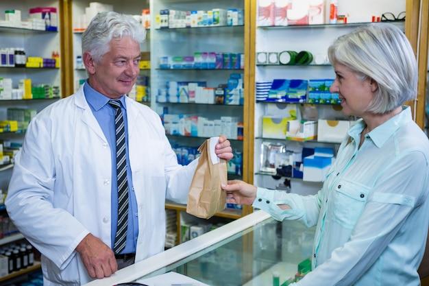 Farmacista che dà il pacchetto di medicina al cliente