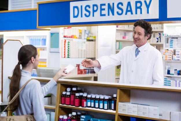 Farmacista che dà la scatola della medicina al cliente