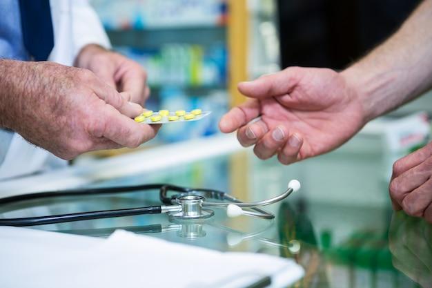 Farmacista che dà medicina al cliente