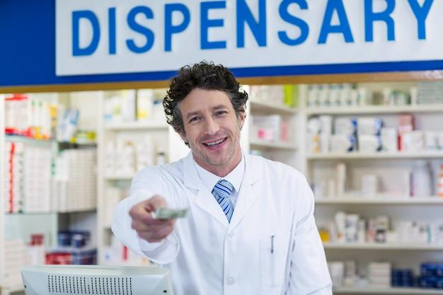 Farmacista che dà soldi al cliente in farmacia