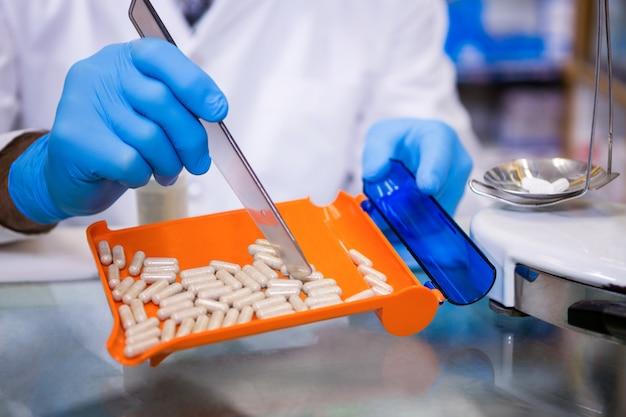 Farmacista che mette le pillole in contenitore