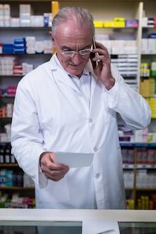 Farmacista che parla sul telefono cellulare mentre controllando prescrizione