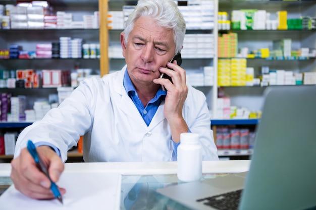 Farmacista che parla sul telefono cellulare mentre scrivendo le prescrizioni
