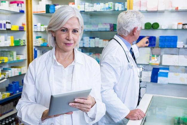 Farmacista che per mezzo della compressa digitale e collega che controllano le medicine