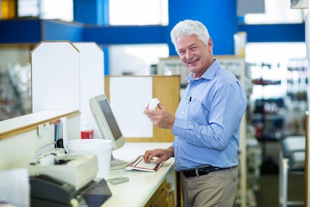 Farmacista che registra record di prescrizione tramite il computer in farmacia