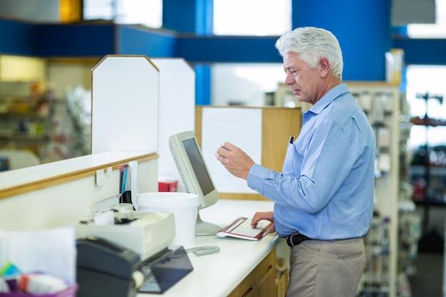 Farmacista che registra record di prescrizione tramite il computer