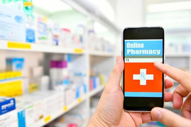 Farmacista che utilizza smart phone mobile per la barra di ricerca su esposizione nello spazio degli scaffali della farmacia della farmacia concetto medico online.