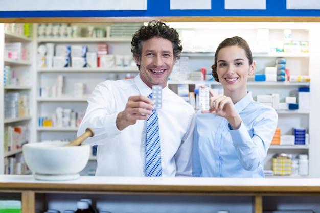 Farmacista sorridente che mostra medicina nella farmacia