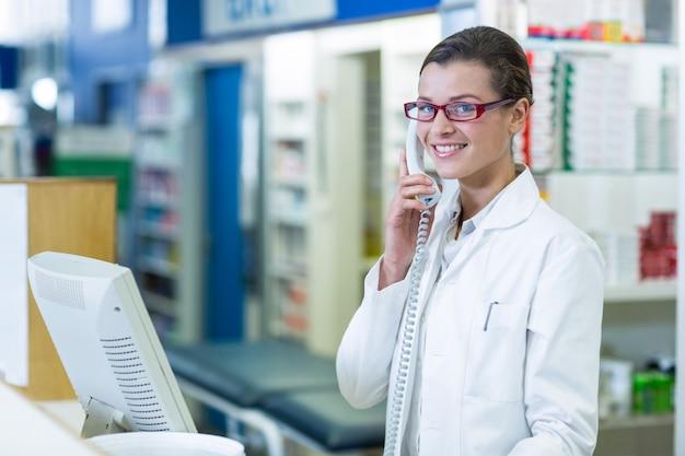 Farmacista sorridente che parla sul telefono in farmacia