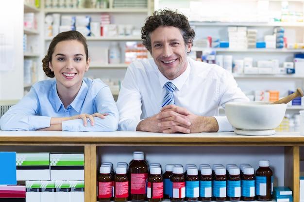 Farmacisti sorridenti che si appoggiano al contatore in farmacia