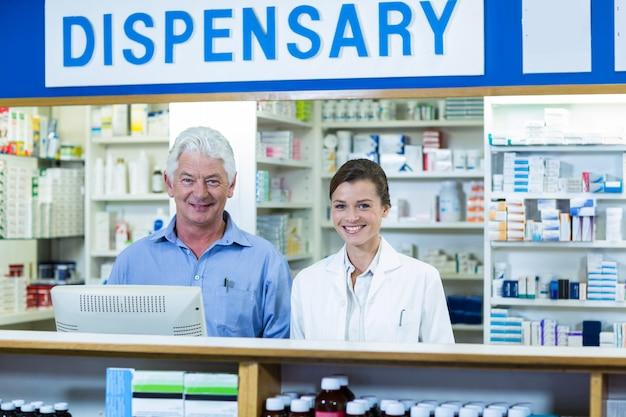 Farmacisti sorridenti che stanno al contatore in farmacia