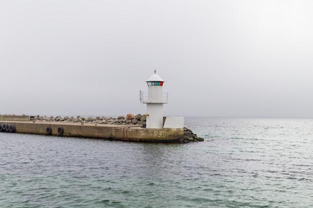 Faro alla fine di un molo di pietra sull'isola di ven, nel sud della svezia.