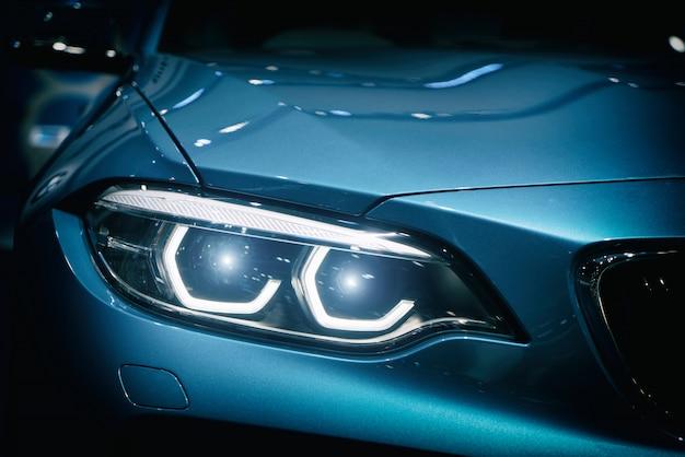 Faro dell'automobile e cappuccio dell'automobile sportiva blu potente con abbagliamento blu su fondo scuro.