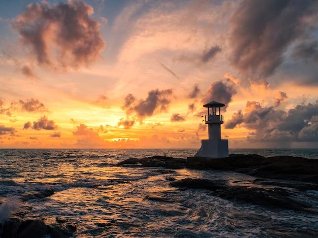 Faro nel mare e luce della sera.