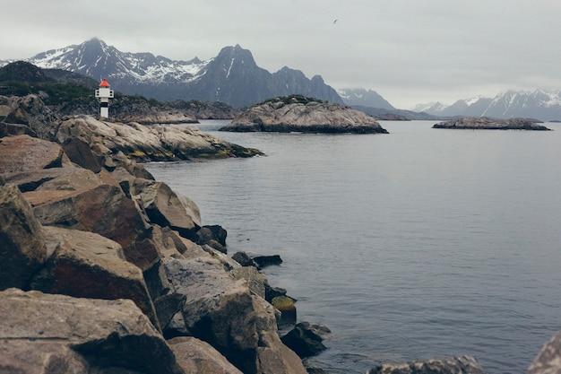 Faro nelle acque selvagge e remote del mare del nord atlantico, tra le rocce di un porto nordico.