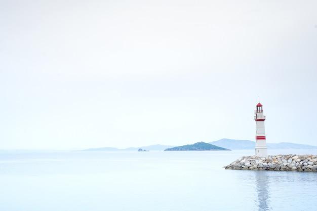 Faro solitario su una strada di pietra in mezzo al mare con vista sulle montagne e nebbia