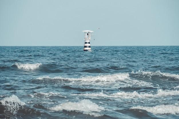 Faro sul mare con la bandiera della thailandia.