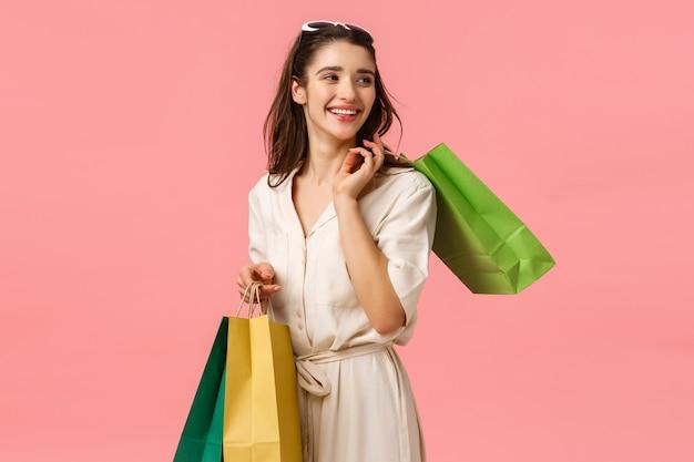Fascino rilassato e spensierato, ragazza carina femminile in abito con borse della spesa e svolta a destra con un bel sorriso felice, godendo di negozi alla moda, in piedi muro rosa