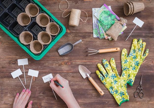 Fasi di piantare semi, preparazione, mani di donna che scrivono i nomi delle piante, strumenti di giardinieri e utensili