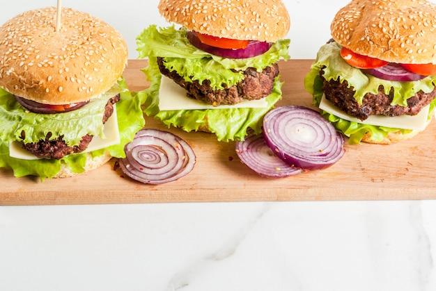 Fast food. cibo malsano. hamburger saporiti freschi deliziosi con la cotoletta di manzo, gli ortaggi freschi e il formaggio su fondo bianco.
