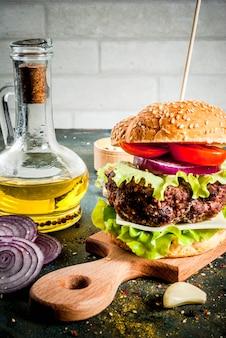 Fast food. cibo malsano. hamburger saporito fresco delizioso con la cotoletta di manzo, gli ortaggi freschi e il formaggio su calcestruzzo blu scuro. copyspace