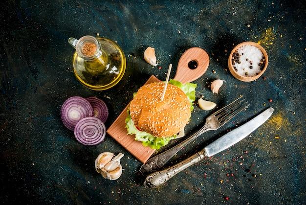 Fast food. cibo malsano. hamburger saporito fresco delizioso con la cotoletta di manzo, gli ortaggi freschi e il formaggio su superficie di calcestruzzo blu scuro. copia spazio vista dall'alto