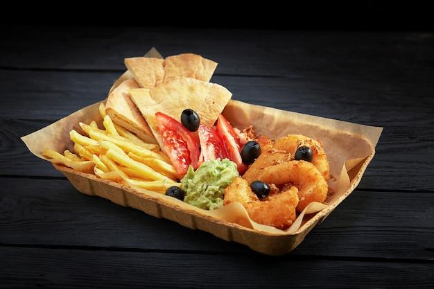 Fast food e malsano concetto di mangiare - close up di patatine fritte, pita e gamberi, salsa di pomodoro e guacamole sulla scatola di carta