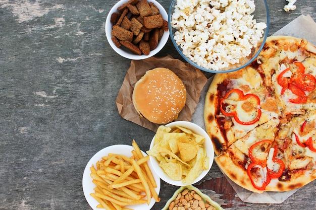 Fast food su sfondo di legno vecchio. concetto di cibo spazzatura. vista dall'alto. lay piatto.