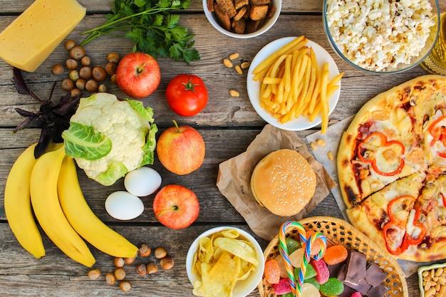 Fastfood e alimenti sani su superficie di legno vecchio. concetto che sceglie nutrizione corretta o di cibo spazzatura. vista dall'alto.