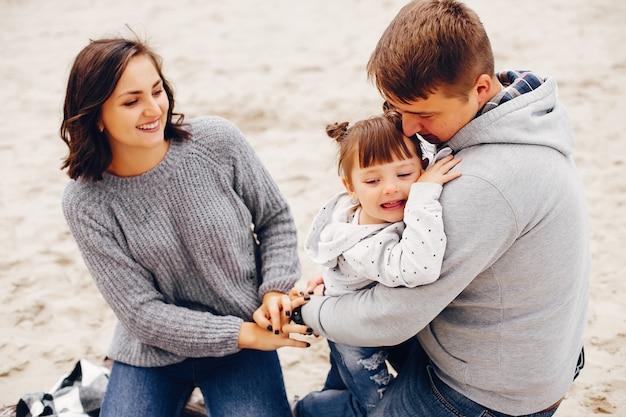 Fathet con la figlia che gioca su una sabbia