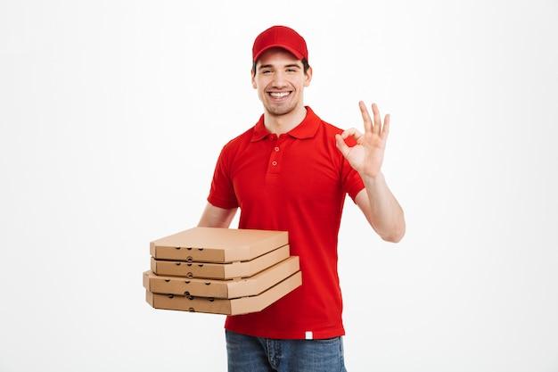 Fattorino 25y in pila rossa della tenuta della maglietta e del cappuccio di scatole di pizza e mostrando segno giusto, isolato sopra spazio bianco
