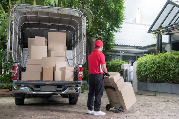 Fattorino asiatico che indossa maschera e guanti in uniforme rossa che consegna la cassetta dei pacchi al destinatario durante l'epidemia di covid-19