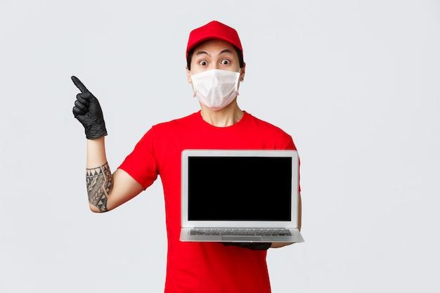 Fattorino asiatico impressionato e scioccato in uniforme rossa, cappuccio, laptop portatile, pubblicità dello schermo, puntamento nell'angolo in alto a sinistra nel sito di shopping online, corriere consegna gli ordini dei clienti