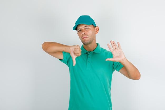 Fattorino che gesturing no e che mostra il pollice giù in maglietta e berretto verdi