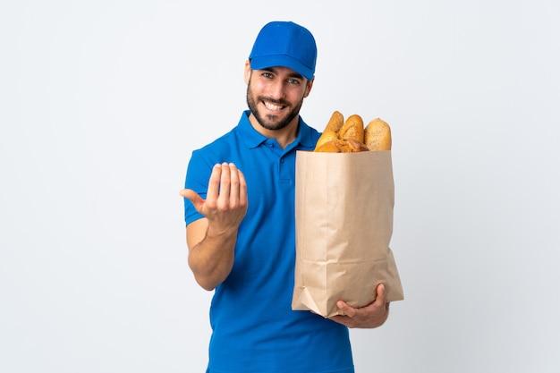 Fattorino che giudica una borsa piena di pani isolati sulla parete bianca che invita a venire con la mano. felice che tu sia venuto